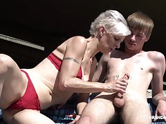 Kinky granny in thongs sucks a beamy abiding penis of one young guy