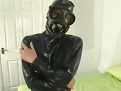 Gasmask Girl in Rubber Accommodate on Bed